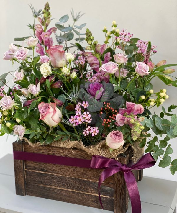 Purple pink and cream flowers in a wooden crate