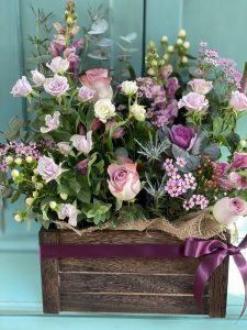 FLowers in a crate display on a chest of drawers