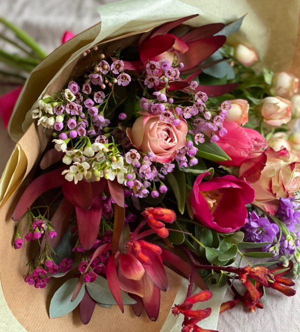 A bouquet of flowers wrapped in brown paper