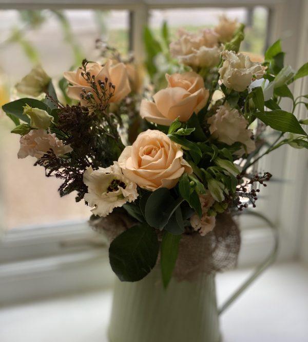 Peach flowers displayed in a jug